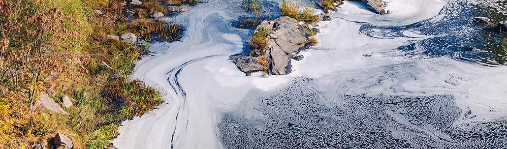 Verschmutzter Fluss mit Schaum auf der Oberfläche