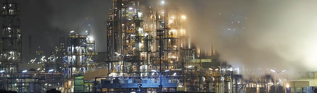 Große Ölraffinerieanlage umhüllt von Rauch