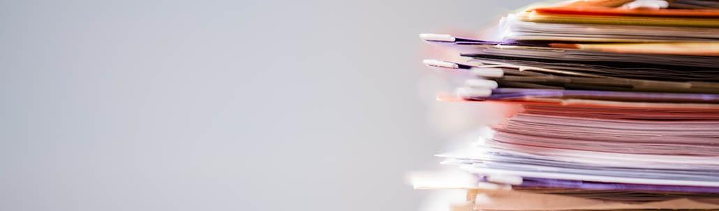 Stapel mit farbigen Druckunterlagen vor grauem Hintergrund